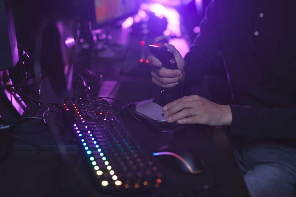 Gamer manuseando um joystick, além de teclado e mouse próximos